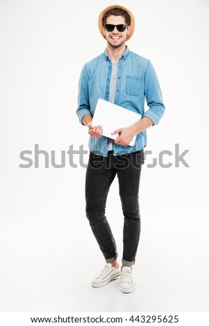 Full length of happy young man in hat and sunglasses holding laptop over white background - stock photo