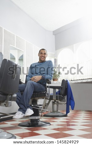 Full length of happy young man sitting on chair in hair salon - stock photo