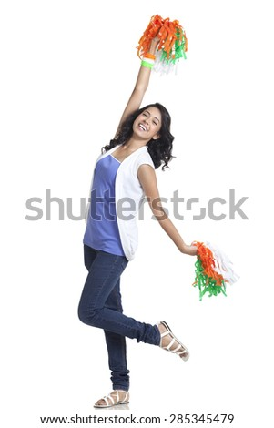 Full length of happy young woman cheering with Indian tricolor pom poms over white background - stock photo