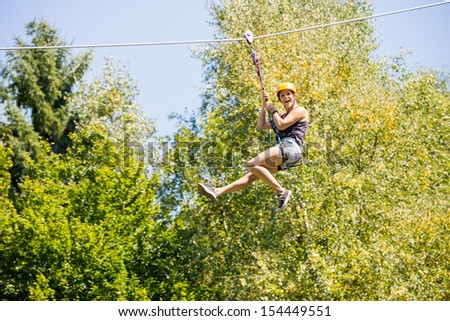 Full length of happy young woman hanging on zip line against trees in forest - stock photo