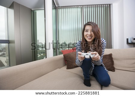Full length of happy young woman playing video game on sofa at home - stock photo