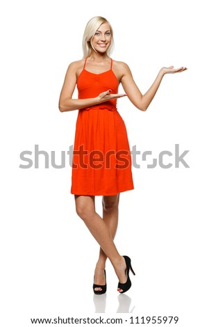 Full length of happy young woman showing a product - empty copy space on the open hand palm, over white background - stock photo