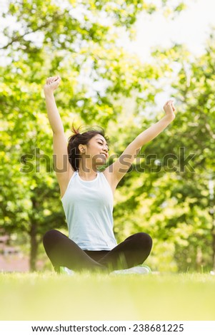 Full length of healthy and beautiful young woman stretching hands in park