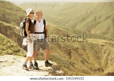 Full length of hiking couple standing on top of mountain - stock photo