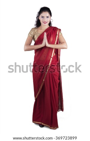 Full length of indian young woman wearing traditional clothes with greeting gesture, isolated on white background - stock photo