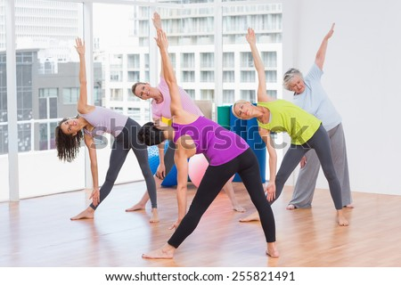 Full length of instructor guiding friends in stretching exercise at gym - stock photo