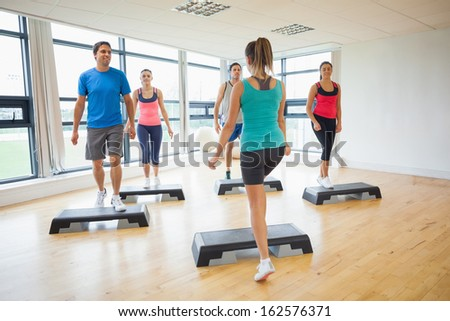 Full length of instructor with fitness class performing step aerobics exercise in gym - stock photo
