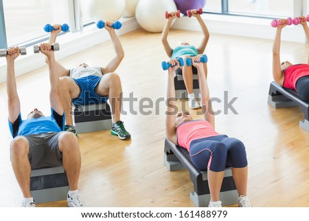 Full length of instructor with fitness class performing step aerobics exercise with dumbbells in a gym - stock photo