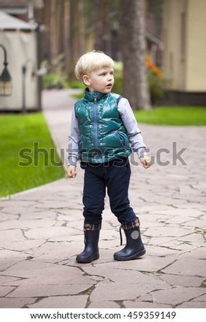 Full length of little blonde boy, spring outdoors