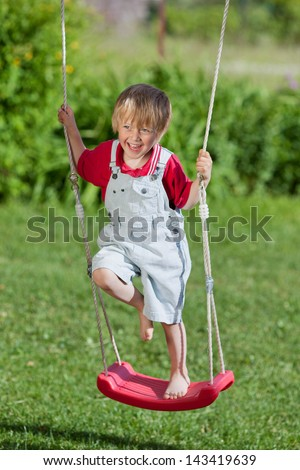 Full length of little boy standing on swing at playground - stock photo