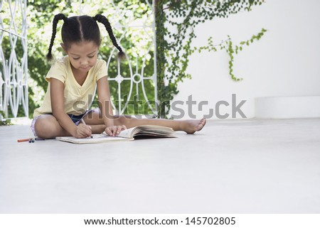 Full length of little girl drawing with crayons on porch - stock photo