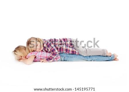 Full length of little girl lying on sister isolated over white background - stock photo
