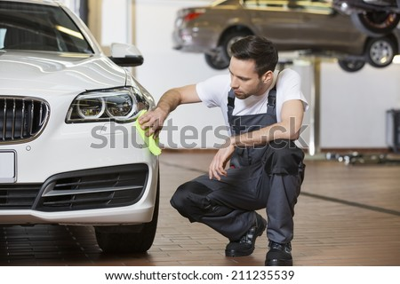 Full length of maintenance engineer cleaning car in workshop - stock photo