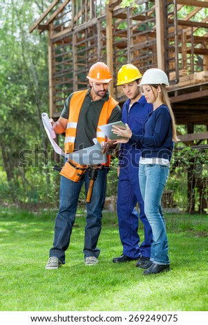 Full length of male and female architects using tablet computer while reviewing blueprint at construction site - stock photo