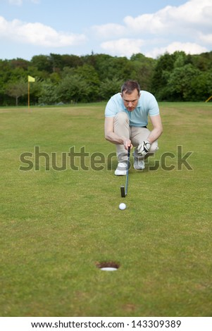 Full length of male golfer crouching while aiming at ball at golf course - stock photo