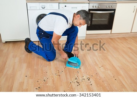 Full length of male janitor sweeping floor with brush and dustpan in kitchen - stock photo