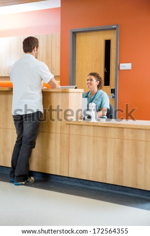 Full length of male patient conversing with nurse at reception desk in hospital - stock photo