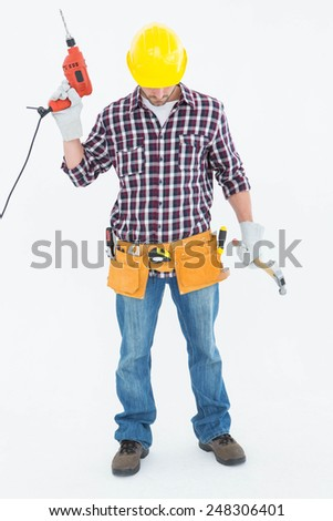 Full length of male repairman holding drill machine and hammer on white background - stock photo