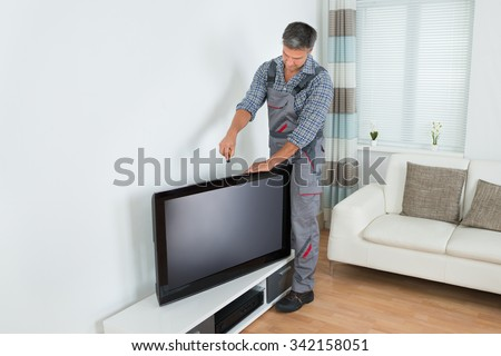 Full length of male technician installing television at home - stock photo