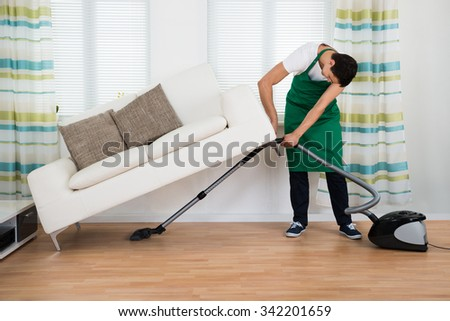Full length of man lifting couch while cleaning hardwood floor with vacuum cleaner at home - stock photo