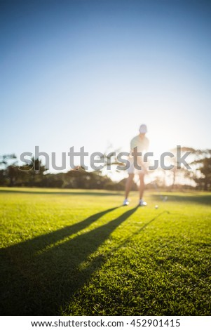 Full length of man playing golf on field against clear sy - stock photo