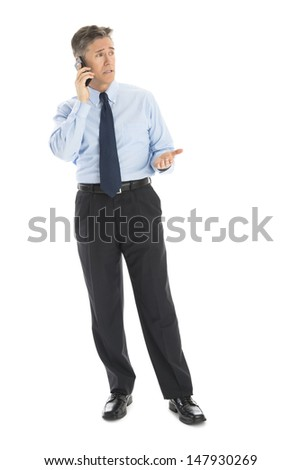 Full length of mature businessman gesturing while using smart phone against white background - stock photo