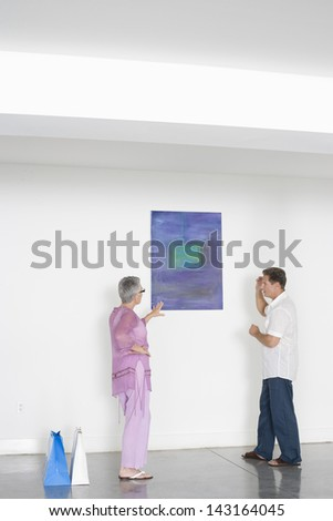 Full length of mature couple discussing over painting in art gallery - stock photo
