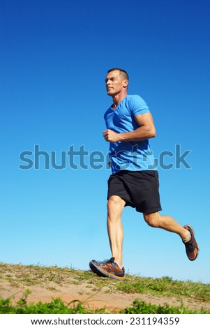 Full length of mature male athlete running on field against clear blue sky - stock photo