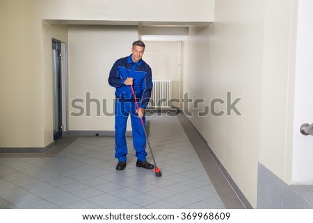 Full length of mature male worker with broom cleaning office corridor - stock photo