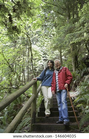 Full length of mature man and middle aged woman walking on forest stairs - stock photo