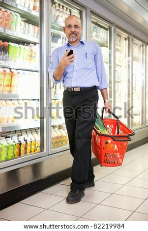 Full length of mature man in shopping store carrying basket and using mobile phone while walking - stock photo