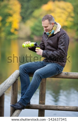 Full length of mature man pouring coffee from thermos while sitting on fence against lake - stock photo