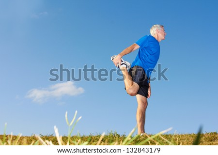 Full length of mature man stretching muscles during exercise against sky. Horizontal shot. - stock photo