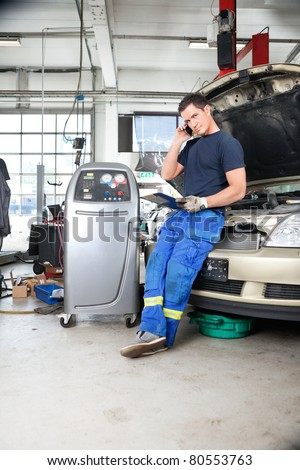 Full length of mechanic discussing repairs with customer on phone - stock photo