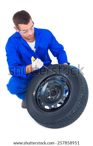 Full length of mechanic working on tire over white background - stock photo