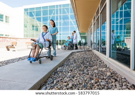 Full length of medical team with patients on wheelchairs at hospital courtyard - stock photo