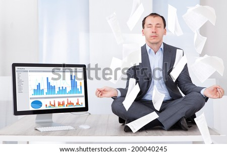 Full length of mid adult businessman meditating while documents falling over him by computer in office - stock photo