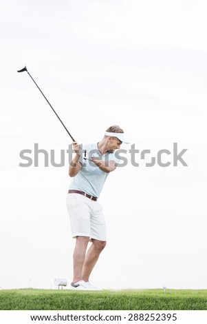 Full-length of mid-adult man swinging golf club against clear sky - stock photo