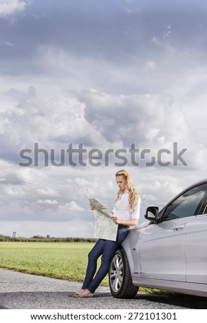 Full length of mid adult woman leaning on car while reading map at countryside - stock photo