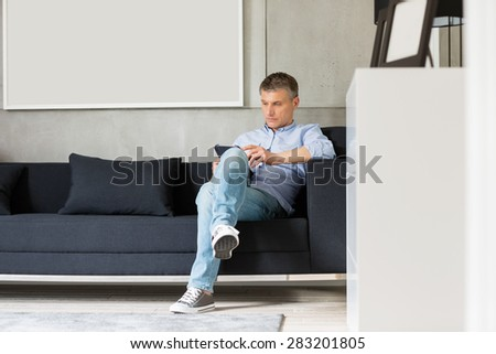 Full-length of Middle-aged man using digital tablet on sofa - stock photo