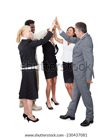 Full length of multiethnic business team joining hands over white background - stock photo