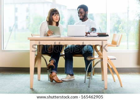 Full length of multiethnic college friends using technologies while studying in library - stock photo
