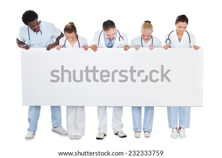 Full length of multiethnic medical team looking at blank billboard over white background - stock photo