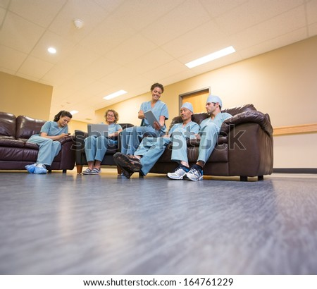 Full length of multiethnic medical team using technologies in hospital's waiting room - stock photo
