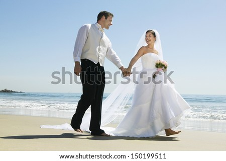 Full length of newlywed couple holding hands while walking on beach - stock photo