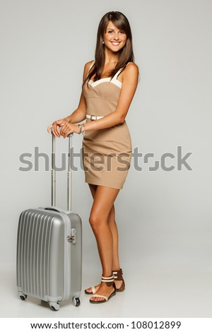 Full length of of trendy young woman in elegant beige dress standing with silver travel bag, over gray background