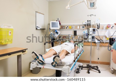 Full length of patient lying on bed in hospital room - stock photo