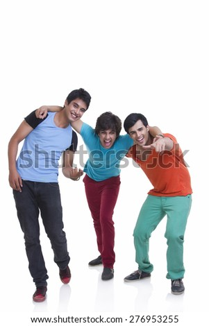 Full length of playful young male friends with arm around over white background - stock photo