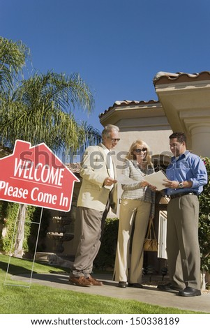 Full length of real estate agent discussing contract with couple in front of home - stock photo