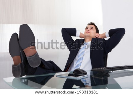 Full length of relaxed businessman daydreaming in office - stock photo